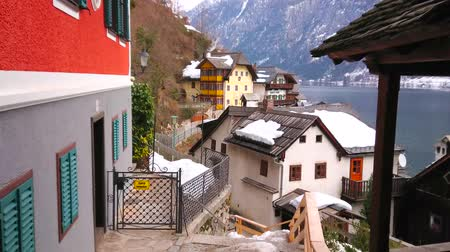 snowbound : HALLSTATT, AUSTRIA - FEBRUARY 25, 2019: The scenic snowy houses in hilly street of old town with Hallstatter see (lake) and Hoher Sarstein mountain slope on background, on February 25 in Hallstatt.