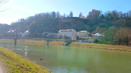 bell tower : The walk along Elisabeth embankment of Salzach river with a view on Monchsberg hill, covered with forest and the Mullner pedestrian bridge (Mullnersteg), Salzburg, Austria. Stock Footage