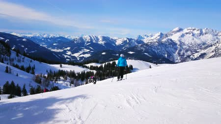 hegytömb : GOSAU, AUSTRIA - FEBRUARY 26, 2019: The group of skiers starts the downhill from top of Zwieselalm mountain, surrounded by snowbound peaks of Dachstein West massif of Alps, on February 26 in Gosau.