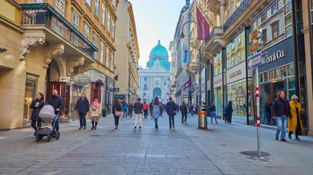 hofburg : VIENNA, AUSTRIA - FEBRUARY 17, 2019: Walk along the Kohlmarkt, one of the central shopping areas of the city, leading to St Michael Square (Michaelerplatz) and Hofburg Palace, on February 17 in Vienna