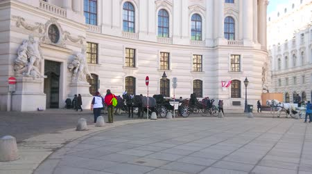 hofburg : VIENNA, AUSTRIA - FEBRUARY 17, 2019: The vintage horse-drawn carriages wait the tourists at the Hofburg Imperial palace in St Michaels square (Michaelerplatz), on February 17 in Vienna.