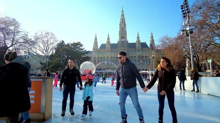 rathauspark : VIENNA, AUSTRIA - FEBRUARY 17, 2019: The crowded ice skating rink in Rathaus square with a view on Neo Gothic building of Town Hall (Rathaus) with tall clock tower, on February 17 in Vienna.