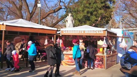 rathauspark : VIENNA, AUSTRIA - FEBRUARY 17, 2019: Market stalls with snacks and sweets are neighboring with ice skating rink in crowded Rathaus square and attract tourist and sportsmen, on February 17 in Vienna.