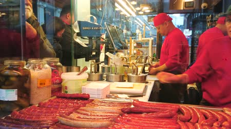 szószok : VIENNA, AUSTRIA - FEBRUARY 17, 2019: The cooks in fast food kiosk prepare tasty hot dogs with traditional sausages (wurst) with spicy sauces and vegetable salads, on February 17 in Vienna. Stock mozgókép