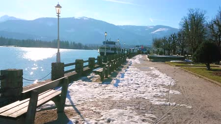 ferry terminal : ST WOLFGANG, AUSTRIA - FEBRUARY 23, 2019: Relax in small park on embankment of Wolfgangsee lake with small benches, old-styled streetlights and ferry port on background, on February 23 in St Wolfgang. Stock Footage