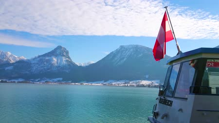 opposite : ST WOLFGANG, AUSTRIA - FEBRUARY 23, 2019: Bright blue rippled surface of Wolfgangsee lake with waving Austrian flag on the ferrys stern and rocky Alps on opposite bank, on February 23 in St Wolfgang.
