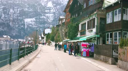 hallstatter see : HALLSTATT, AUSTRIA - FEBRUARY 25, 2019: Seestrasse stretches along the bank of Hallstatter see (lake) and boasts large amount of tourist stores, cafes and hotels, on February 25 in Hallstatt. Stock Footage