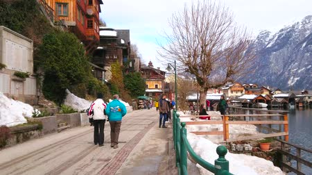 avusturya : HALLSTATT, AUSTRIA - FEBRUARY 25, 2019: Walk the quiet winter lakeside promenade - Seestrasse with snowdrifts on the sides and colorful wooden houses on mountain slope, on February 25 in Hallstatt.