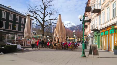 snowbound : BAD ISCHL, AUSTRIA - FEBRUARY 26, 2019: The crowded outdoor terrace of the popular city restaurant, located in Schropferplatz and surrounded by historical edifices, on February 26 in Bad Ischl.