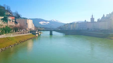 rampart : Enjoy the sunny day in Salzburg, walking along the Makartsteg foot bridge in old town, overlooking historic quarters, snowy Alps and Salzach river, Austria. Stock Footage