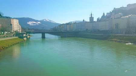 citadela : SALZBURG, AUSTRIA - FEBRUARY 27, 2019: Watch the old town buildings, Salzach river and its banks, towering Hohensalzburg Fortress from the Makartsteg bridge, on February 27 in Salzburg