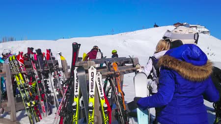 ski run : ZELL AM SEE, AUSTRIA - FEBRUARY 28, 2019: The ski stands in front of the Schmitten mountain slope with many sportsmen, going downhill, on February 28 in Zell Am See.
