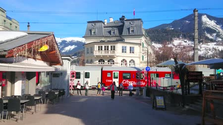 barriers : ZELL AM SEE, AUSTRIA - FEBRUARY 28, 2019: Seegasse street with a view on cafes, shops, Grand hotel, riding train and pedestrians, waiting at barrier of railroad crossing, on February 28 in Zell Am See