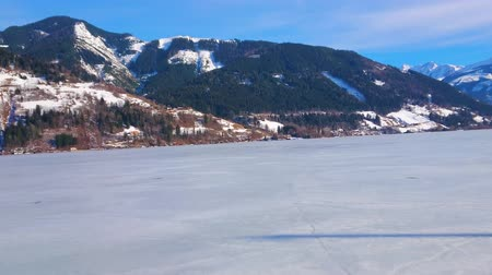 elisabeth : ZELL AM SEE, AUSTRIA - FEBRUARY 28, 2019: Panorama from embankment of Elisabeth park with a view on Zeller see, covered with ice, Alps and Grand Hotel on the lakes bank, on February 28 in Zell Am See Stock Footage