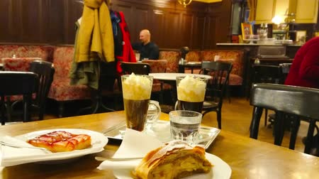 alkoholos : VIENNA, AUSTRIA - FEBRUARY 18, 2019: Enjoy the evening in Cafe Sperl with traditional desserts - alcoholic coffee drinks with cake and strudel in classic Viennese interior, on February 18 in Vienna. Stock mozgókép