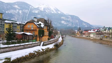margem do rio : BAD ISCHL, AUSTRIA - FEBRUARY 20, 2019: Panorama of the banks of Traun river with old town quarters, historic housing and foggy Katrin Mount on the background, on February 20 in Bad Ischl
