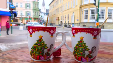 столовая гора : BAD ISCHL, AUSTRIA - FEBRUARY 20, 2019: Enjoy hot tea from the Christmas mugs in outdoor cafe with a view on historic townhouses in Pfarrgasse street, on February 20 in Bad Ischl Стоковые видеозаписи