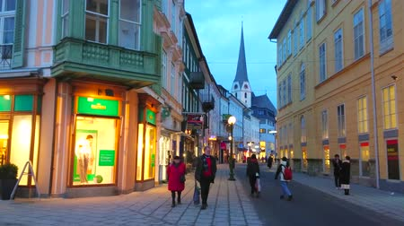 evangelical : BAD ISCHL, AUSTRIA - FEBRUARY 20, 2019: Bright showcases of the fashion stores illuminate the evening Pfarrgasse street, running along the old townhouses and Parish church, on February 20 in Bad Ischl