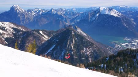extreme : EBENSEE, AUSTRIA - FEBRUARY 24, 2019: The view on Traunsee lake valley, roofs of Ebensee, Dachstein Alps and red gondola of Feuerkogel cable car, rising along a snowy slope, on february 24 in Ebensee Stock Footage