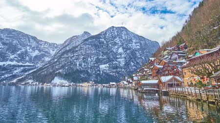 hegytömb : Enjoy fast running clouds over the scenic Hallstatter see from the lakeside promenade of old Hallstatt with its colorful wooden houses and huge Dachstein Alps, Salzkammergut, Austria.
