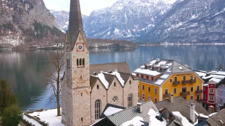 parrocchia : Hallstatt town center with a view on Evangelical Parish Church, old townhouses, embankment of Hallstatter see (lake) and snowy Dachstein Alps on the background, Salzkammergut, Austria.