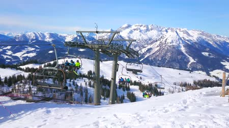 chairlift : GOSAU, AUSTRIA - FEBRUARY 26, 2019: The chairlift, riding along the snowy slope of Zwieselalm mount, with a view on peaks of Dachstein West Alps on the background, on February 26 in Gosau. Stock Footage