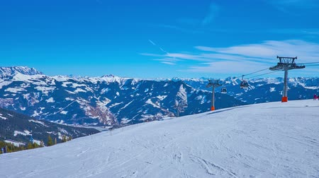 snowboarden : The skiers and other sportsmen enjoy the Schmitten mountain winter resort with fine pistes, developed cableway network and exciting views on snowy Alps, Zell am See, Austria.