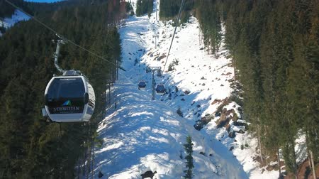 ski run : ZELL AM SEE, AUSTRIA - FEBRUARY 28, 2019: The modern gondolas of Trassxpress cable car runs along the steep slope of Schmitten mountain with lush forests and snowy rocks, on February 28 in Zell Am See