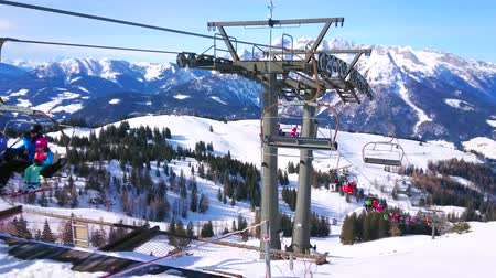 chairlift : GOSAU, AUSTRIA - FEBRUARY 26, 2019: The chairlift carries the sportsmen up on the Zwieselalm mountain in Dachstein West Alps, on February 26 in Gosau. Stock Footage