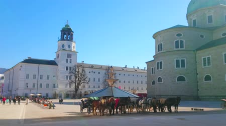 cavalo vapor : SALZBURG, AUSTRIA - FEBRUARY 27, 2019: The Residenzplatz square with a view on Residence Palace, famous carillon tower, apse of the Cathedral and horse-drawn carriages, on February 27 in Salzburg