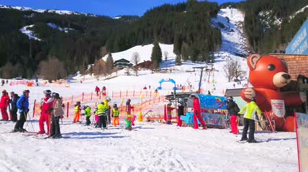 ski run : ZELL AM SEE, AUSTRIA - FEBRUARY 28, 2019: The crowded children ski area at the foot of Sonnenalm mount with large inflatable bear, attracting kids here, on February 28 in Zell Am See.