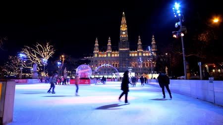 rathauspark : VIENNA, AUSTRIA - FEBRUARY 18, 2019: The evening Rathaus square with a view on crowded ice skating rink in front of brightly illuminated Town Hall (Rathaus), on February 18 in Vienna. Stock Footage