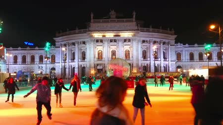 rathauspark : VIENNA, AUSTRIA - FEBRUARY 18, 2019: The evening Burgtheater with riding trams and brightly illuminated ice skating rink in the Rathausplatz square on foreground, on February 18 in Vienna. Stock Footage