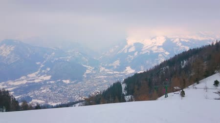 hegytömb : The Mount Katrin overlooks foggy valley of Bad Ischl, bright gondolas of cable car and snowy slopes of Dachstein Alps, Salzkammergut, Austria. Stock mozgókép