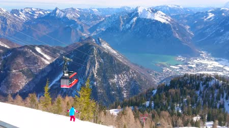 hegytömb : EBENSEE, AUSTRIA - FEBRUARY 24, 2019: The scenic landscape of Salzkammergut with riding tram of Feuerkogel cable car, Traunsee lake valley and skiers, going downhill, on february 24 in Ebensee.