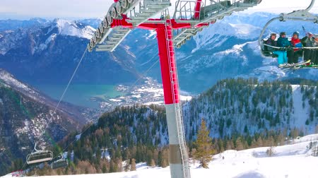 hegytömb : EBENSEE, AUSTRIA - FEBRUARY 24, 2019: The chairlift with sportsmen rides to the top of Feuerkogel with a view on Traunsee lake valley and Alpine scenery, on february 24 in Ebensee.