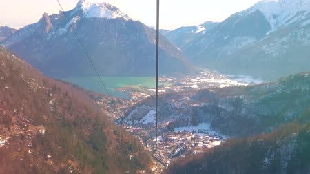 hegytömb : The breathtaking journey on Feuerkogel cable car over the slopes of Dachstein Alps with a view on Ebensee, Traunsee lake, coniferous forests and snowy hills, Salzkammergut, Austria. Stock mozgókép