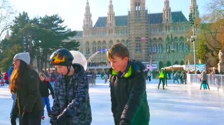 eski : VIENNA, AUSTRIA - FEBRUARY 17, 2019: Rathaus square in front of historical Town Hall is occupied with large multilevel ice skating rink, full of kids, youth and families, on February 17 in Vienna. Stok Video