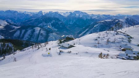 hegytömb : Enjoy winter mountain landscape from the slope of Feuerkogel mount with a view on the maze of pistes, numerous skiers, riding chairlift and foggy Dachstein Alps on background, Salzkammergut, Austria.