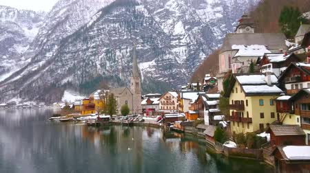 evangelical : The bank of Hallstatter see is occupied with dense colorful houses, stone Parish church with tall spire and snowy Dachstein Alps on background, Hallstatt, Salzkammergut, Austria.