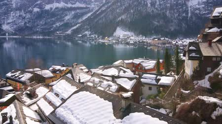 hallstatter see : The densely located snowy roofs of old Hallstatt houses with smoke, slowly coming out of chimneys and Hallstattersee lake, reflecting rocky Dachstein Alps, Salzkammergut, Austria.