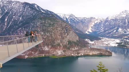 hegytömb : HALLSTATT, AUSTRIA - FEBRUARY 21, 2019: Tourists enjoy the Alpine landscape and Hallstatter see (lake) from the World Heritage View lookout platform on Salzberg mountain, on February 21 in Hallstatt