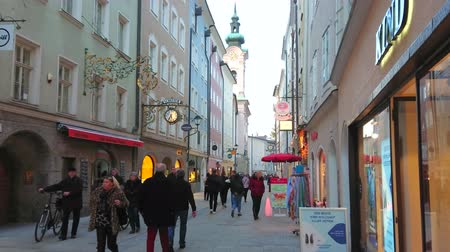 art : SALZBURG, AUSTRIA - FEBRUARY 27, 2019: The crowded Linzergasse street with many stores, cafes, art galleries, historic edifices and belfry of St Sebastian church, on February 27 in Salzburg. Wideo