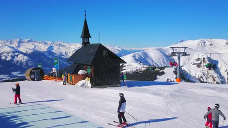 elisabeth : ZELL AM SEE, AUSTRIA - FEBRUARY 28, 2019: The skiers skate from the chairlift to the Schmitten mount pistes along the old wooden Elisabeth chapel, on February 28 in Zell Am See.