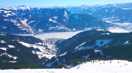ski run : The stunning winter landscape from the top of Schmitten mount with a view on frozen Zeller see, Alpine slopes and riding tram of Schmittenhohebahn cable car, Zell am See, Austria. Stock Footage