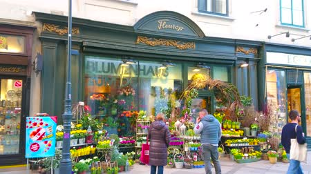 összeg : VIENNA, AUSTRIA - FEBRUARY 19, 2019: Flower shop with vintage showcase and large amount of bouquets and plants in pots in front of the entrance, located in Stephansplatz, on February 19 in Vienna.