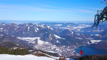 ski run : The stunning scenery of Eastern Alps of Salzkammergut with a view on Wolfgangsee lake, St Gilden tourist village and the tower of Zwolferhorn cable car on the foreground, Austria. Stock Footage