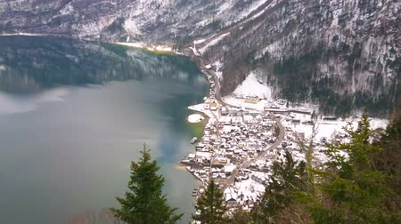 hegytömb : Aerial view on Hallstattersee lake with wind ripples, slopes of Dachstein Alps, tall fir trees and snowy Hallstatt in valley at the foot of Salzberg mount, Salzkammergut, Austria