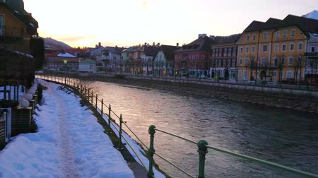 mansão : Enjoy the sunset, walking along the snowy promenade of Traun river with a view on colorful traditional townhouses and bright sky, reflected in rippled waters, Bad Ischl, Salzkammergut, Austria