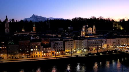 águas : SALZBURG, AUSTRIA - FEBRUARY 27, 2019: Kapuzinerberg hill overlooks twilight city with dark waters of Salzach river and illuminated embankment with old edifices, on February 27 in Salzburg.